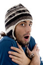 Smart young guy in winter cap shivering from cold Royalty Free Stock Photo