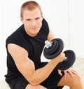 Smart young man exercising with a dumbbell Royalty Free Stock Photo
