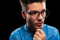 Smart young man wearing denim and glasses while thinking close portrait of looking away from the camera Stock Image