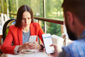 Smartphone addiction concept photo of young women and men sitting in cafe with and do not looking at each other Royalty Free Stock Images