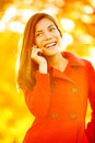 Smartphone autumn woman talking on mobile phone in fall girl having smart conversation in sun flare foliage portrait Stock Photos