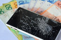 Smartphone with broken display lying on money banknotes on a White background. Royalty Free Stock Photo