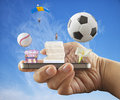 Smartphone entertainment male hand holding a with sports and objects coming out Stock Image