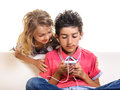 Smartphone gamers kids girl and boy using cell phone for chat social media gaming or listening music using earphones isolated on Royalty Free Stock Photos