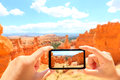 Smartphone taking photo of bryce canyon nature close up mobile phone camera screen photographing beautiful american landscape Stock Photos
