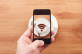 Smartphone taking photograph of free wifi sign on a latte coffe