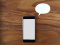 Smartphone thought bubble voice command wooden background Royalty Free Stock Photography