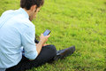 Smartphone young business man sitting on meadow using a smart phone Stock Images
