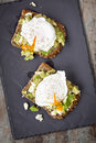 Smashed avocado and feta toast with poached eggs cheese overhead view on dark slate Royalty Free Stock Photography
