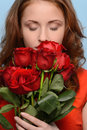 They smell so nicely attractive young woman smelling a bunch of red roses against blue background Stock Photos