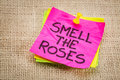 Smell the roses reminder note inspirational on a sticky against burlap canvas Stock Photos