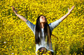 The smell of spring young woman sitting in a field yellow flowers smelling air Royalty Free Stock Photo