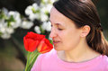 Smelling flower pretty young woman smells outdoor Royalty Free Stock Photo