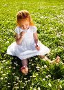Smelling flowers adorable year old girl sitting on the grass and Stock Photography