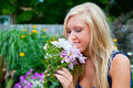 Smelling the flowers a pretty blonde girl a bouquet of Royalty Free Stock Photography