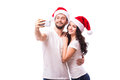 Smile couple in santa hats in love taking romantic self portrait christmas young beautiful selfie photo together with mobile phone Royalty Free Stock Images