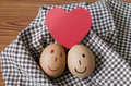 Smile egg love couple in brown kitchen towel on wood table Royalty Free Stock Photos
