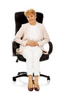 Smile elderly business woman sitting on armchair Stock Photos
