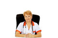 Smile elderly female doctor or nurse sitting behind the desk Royalty Free Stock Photo