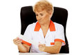 Smile elderly female doctor or nurse sitting behind the desk and holds bandage Royalty Free Stock Photo