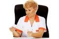 Smile elderly female doctor or nurse sitting behind the desk and holds bandage Royalty Free Stock Photo