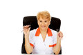 Smile elderly female doctor or nurse sitting behind the desk and holds two pair of glasses Royalty Free Stock Photo
