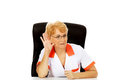 Smile elderly female doctor or nurse sitting behind the desk and overhears a conversation Royalty Free Stock Photo