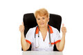 Smile elderly female doctor or nurse sitting behind the desk and shows thumbs up Royalty Free Stock Photo