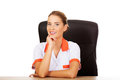 Smile female doctor or nurse sitting behind the desk Royalty Free Stock Photo