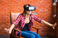 Smile happy woman getting experience using VR-headset glasses of virtual reality at home much gesticulating hands