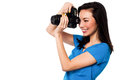 Smile please say cheese beautiful female photographer taking a snap over white Royalty Free Stock Photos