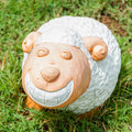 Smile white sheep statue in green grass on daytime Royalty Free Stock Photography