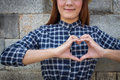 Smile woman holds heart shape on own