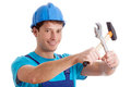 Smiled handy man in blue outfit with hammer and wrench Royalty Free Stock Photos