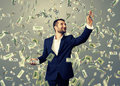 Smiley businessman catching money successful and under dollar s rain Royalty Free Stock Image