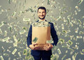 Smiley businessman holding paper bag with money successful and under dollar s rain Stock Photos