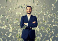 Smiley businessman under dollar s rain successful and over grey background Royalty Free Stock Photo