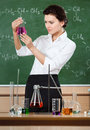 Smiley chemistry teacher examines conical flask Royalty Free Stock Images