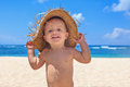 Smiley child with hat has fun on sea sand beach Royalty Free Stock Photo