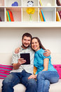 Smiley couple sitting sofa holding tablet pc Royalty Free Stock Photos