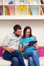 Smiley couple sitting sofa shopping internet Stock Images