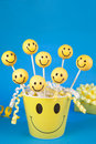 Smiley face cake pops round shaped mini cakes on sticks in a yellow bucket Stock Images