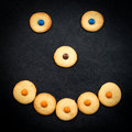 Smiley face of childish cookies on black background Royalty Free Stock Photo