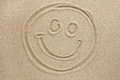 Smiley face painted by in the sand Royalty Free Stock Photo