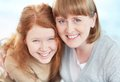 Smiley faces teenage girl and her mother looking at camera with toothy smiles Royalty Free Stock Photo