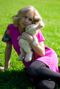 Smiley girl on grass with toy-rabbit Stock Photos