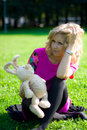 Smiley girl on grass with toy-rabbit Royalty Free Stock Image