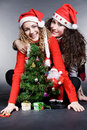 Smiley girls sitting near christmas tree Royalty Free Stock Images