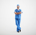 Smiley man in blue scrubs full length portrait of with arms folded looking at camera over light grey background Royalty Free Stock Image