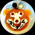 Smiley pancake delicious with drawing using cherry whipped cream sliced orange and chocolate bits Royalty Free Stock Photo